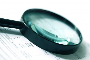 12420575 - magnifying glass over financial figures.  soft focus, cyan tone.