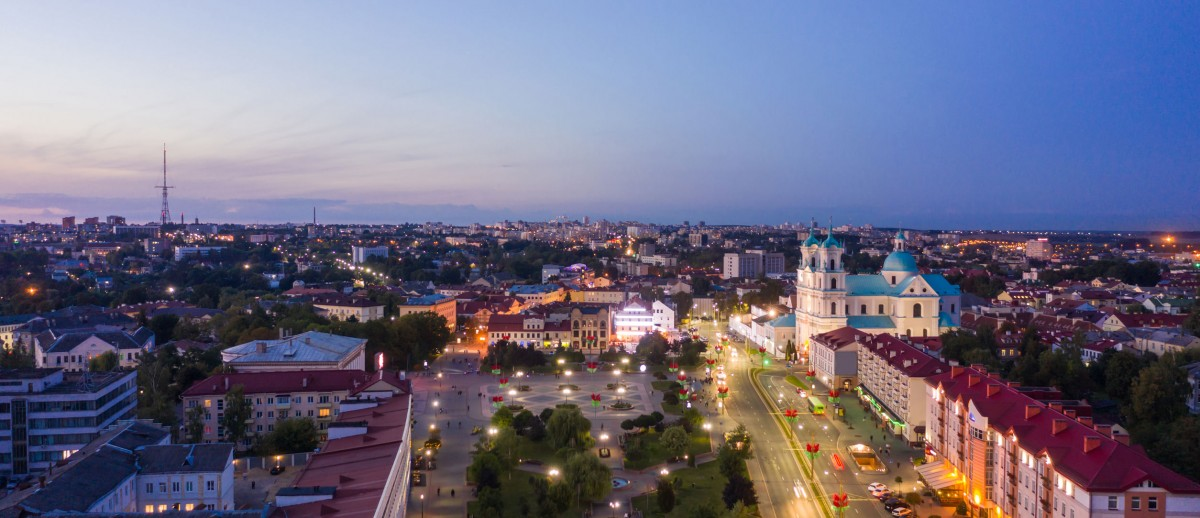 St. Francis Xavier Cathedral And Traffic In Mostowaja And Kirova Streets At Evening In Night Illuminations Lights. Sunset Sky. Grodno city in Belarus